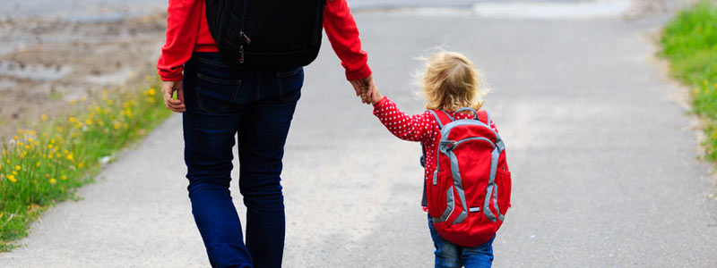 Parent walking hand-in-hand with child