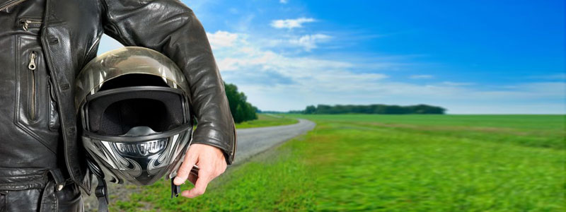Picture of a biker holding a helmet in front of an open road.