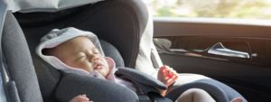 A newborn baby sitting in a car seat in a hot car.